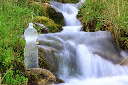 plastic bottle with clean water on a background of the brook  with motion blur photo