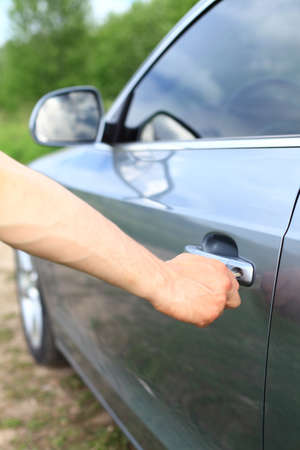 Man unlock grey car door by key photo