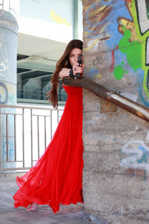 beautiful girl in a red dress with gun photo