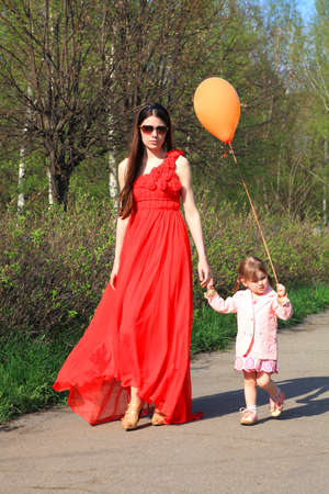 mother walking with daughter in park photo