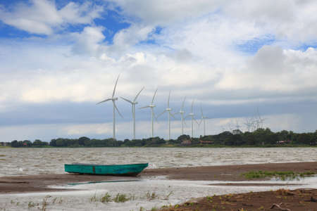 old boat at the background of the modern wind park photo