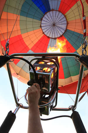 hand controls the burner of the air balloon