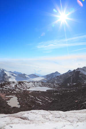 Glacial lake, high mountains and bright sun 写真素材