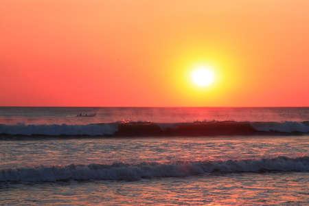 fishing boat sailing among the waves during sunset