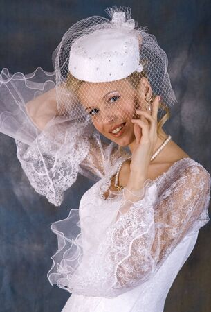 Portrait of the smiling blonde in white dress and hat with veil on bright background. Studio photo Stock Photo