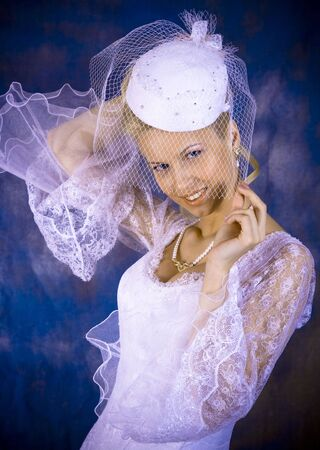 Portrait of the smiling blonde in white dress on bright background. Studio photo Stock Photo