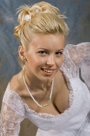 Portr�t der l�chelnden Blondine im wei�en Kleid auf hellem Hintergrund. Foto Studio