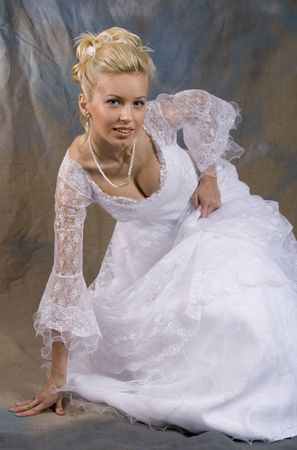 Portrait of the smiling blonde in white dress on bright background. Studio photo photo