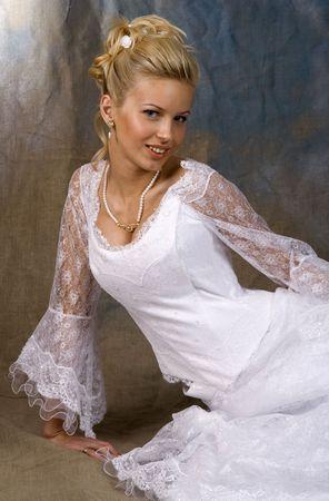 Portrait of the smiling blonde in white dress. Studio photo