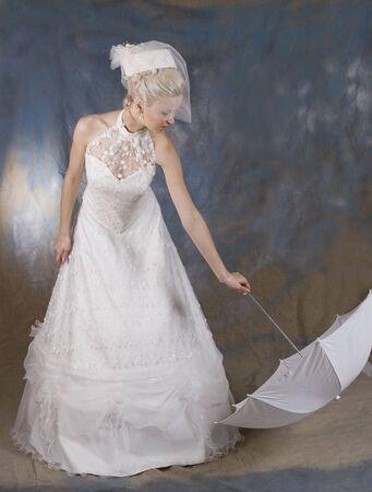 Portr�t des l�chelnden Blondine im wei�en Kleid und Hut mit Schleier und mit Regenschirm in der Hand. Foto Studio