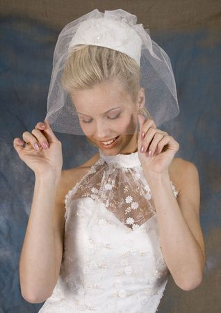 Portrait of the smiling blonde in white dress and hat with veil. Studio photo Stock Photo