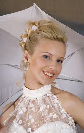 Portr�t des l�chelnden Blondine im wei�en Kleid und mit Regenschirm in der Hand. Foto Studio