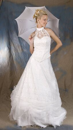 Portrait of the smiling blonde in white dress and with umbrella in hands. Studio photo