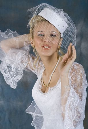 Portrait of the smiling blonde in white dress and hat with veil. Studio photo photo