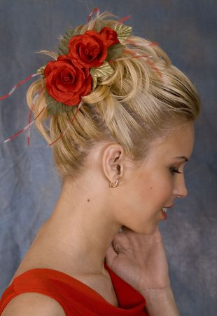 Portrait of the smiling blonde in red dress and with red flower in hair. Studio photo