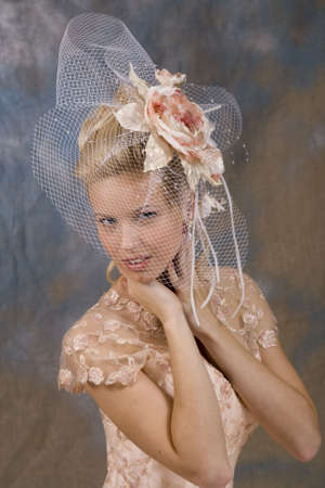 Portrait of the smiling blonde in beige dress and hat with veil. Studio photo photo