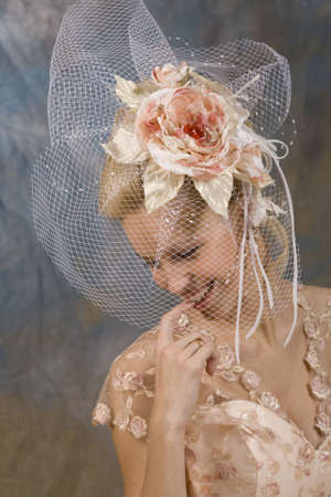 Portrait of the smiling blonde in beige dress and hat with veil. Studio photo Stock Photo