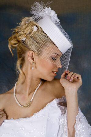 Portr�t des l�chelnden Blondine im wei�en Brautkleid und Hut mit Schleier. Foto-Studio