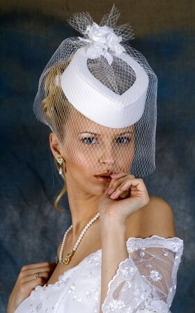 Portrait of the smiling blonde in white wedding dress and hat with veil. Studio photo