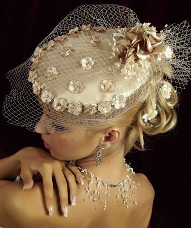 Portrait of the smiling blonde in beige  hat with veil. Studio photo Stock Photo