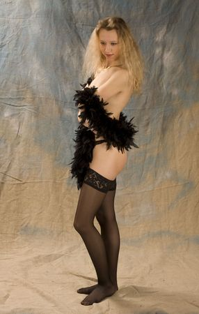 The blonde in black linen costs on brown background and is covered with boa Stock Photo