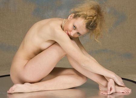 bared: The bared blonde sits on reflecting surface, studio photo