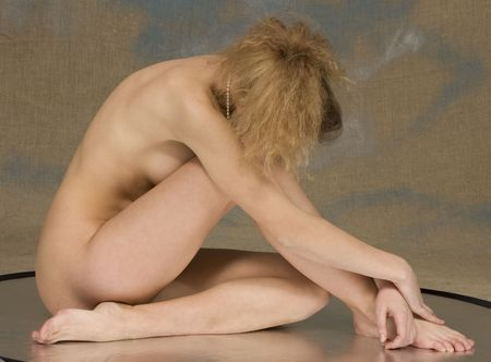 The bared blonde sits on reflecting surface, studio photo