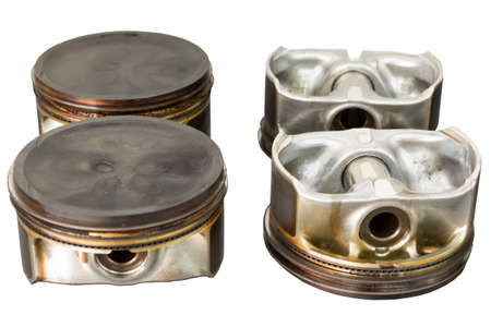 Four pistons with pins and rings that were in use lie on the table. Isolate.