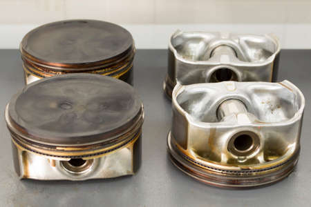 Four pistons with pins and rings that were in use lie on the table