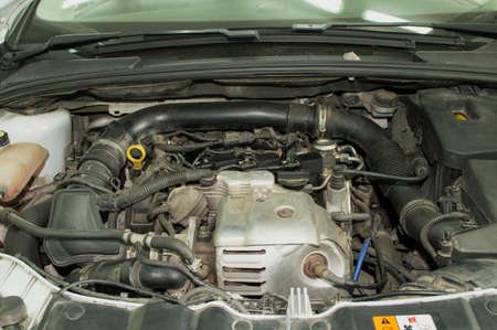 Engine compartment of a white three-cylinder petrol car with an open hood Stockfoto