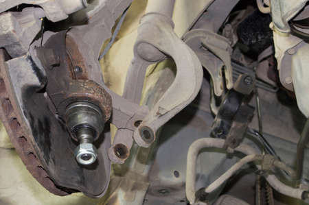 View from the front left wheel of a partially disassembled front suspension of a car in an auto repair shop