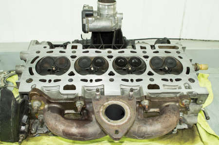 The assembled engine block head with spark plugs, valves, intake and exhaust manifolds and throttle is on the work table in the car repair shop