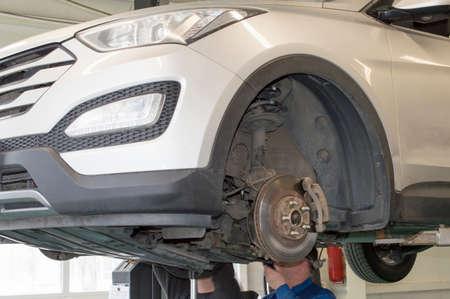 A car mechanic in an auto repair shop makes diagnostics of a light car hung on a lift