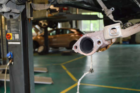 Partially removed exhaust pipe of a car that hangs on a lift in an auto repair shop