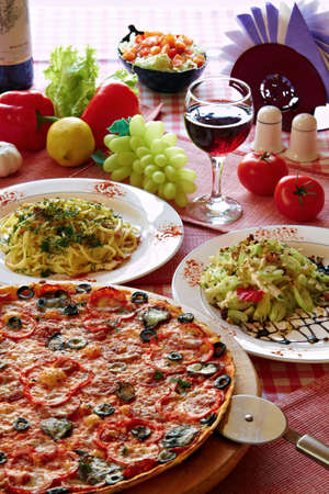 pizza cutter: Classic Italian food setting with pizza, pasta, salad and wine