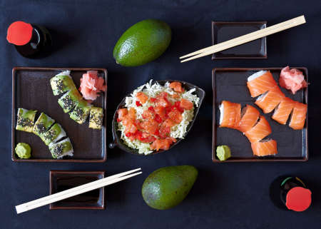 composition of sushi, avocado, soy sauce, ginger, wasabi, salad, chopsticks photo