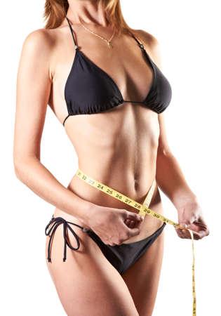 slanke vrouw meten taille met meetlint in inches geà ¯ soleerd op witte achtergrond