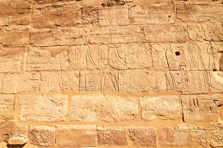 Part of a wall with hieroglyphs and shadow as background photo