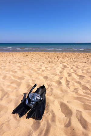 snorkle: Flippers, mask and snorkel lying on sandy beach, vertical orientation