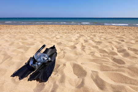 snorkle: Flippers, mask and snorkel lying on sandy beach, horizontal orientation Stock Photo