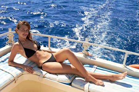 Jonge vrouw in bikini poseren op een jacht op zonnige dag Stockfoto