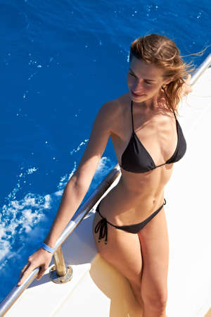 Young woman in bikini standing on yacht at sunny day photo