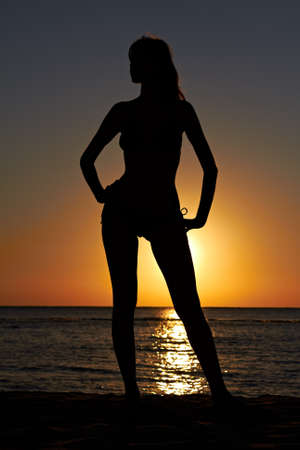Silhouette of woman posing on sea coast at sunrise