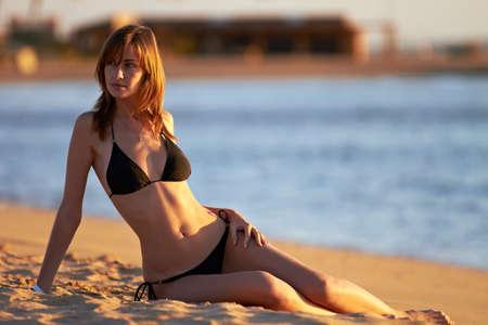 Young woman in bikini posing on sea coast sitting Stock Photo - 12249165