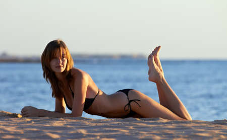 swimsuite: Young woman in bikini posing on sea coast lying