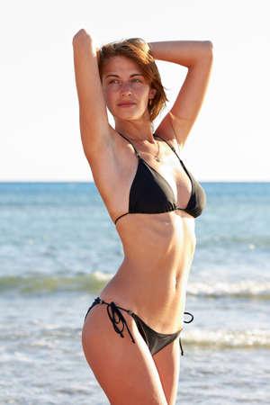 swimsuite: Young woman in bikini posing on sea coast standing