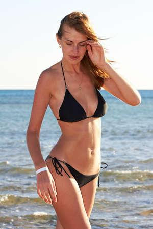 Jonge vrouw in bikini poseren op zee staan