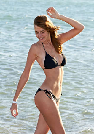 swimsuite: Young woman in bikini posing on sea background standing Stock Photo