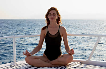 Young woman doing yoga meditation in lotus position on yacht photo