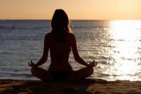 Silhouet van de vrouw in yoga lotus meditatie positie voor het strand